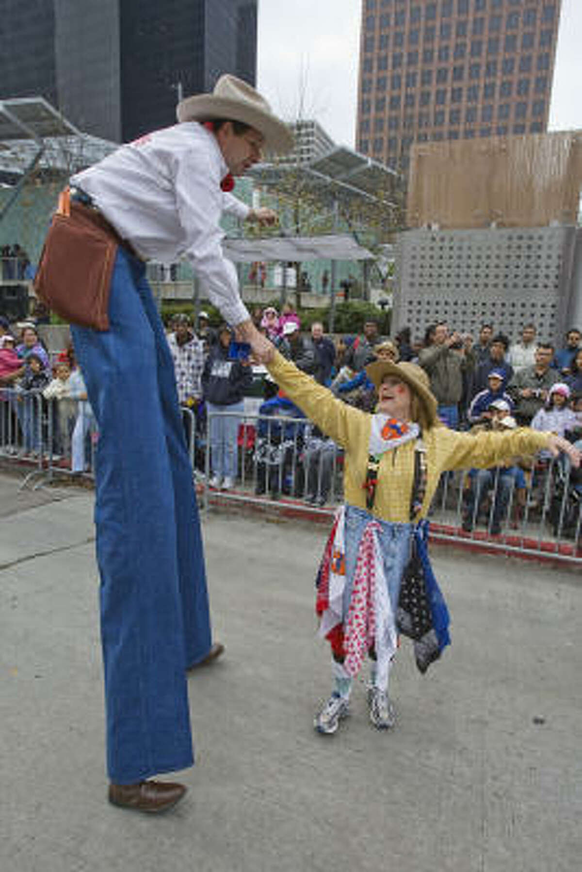 David McCullough, a.k.a. Long Tall Tex, of Tyler, dances with Karen Campbell of Houston along the parade route.
