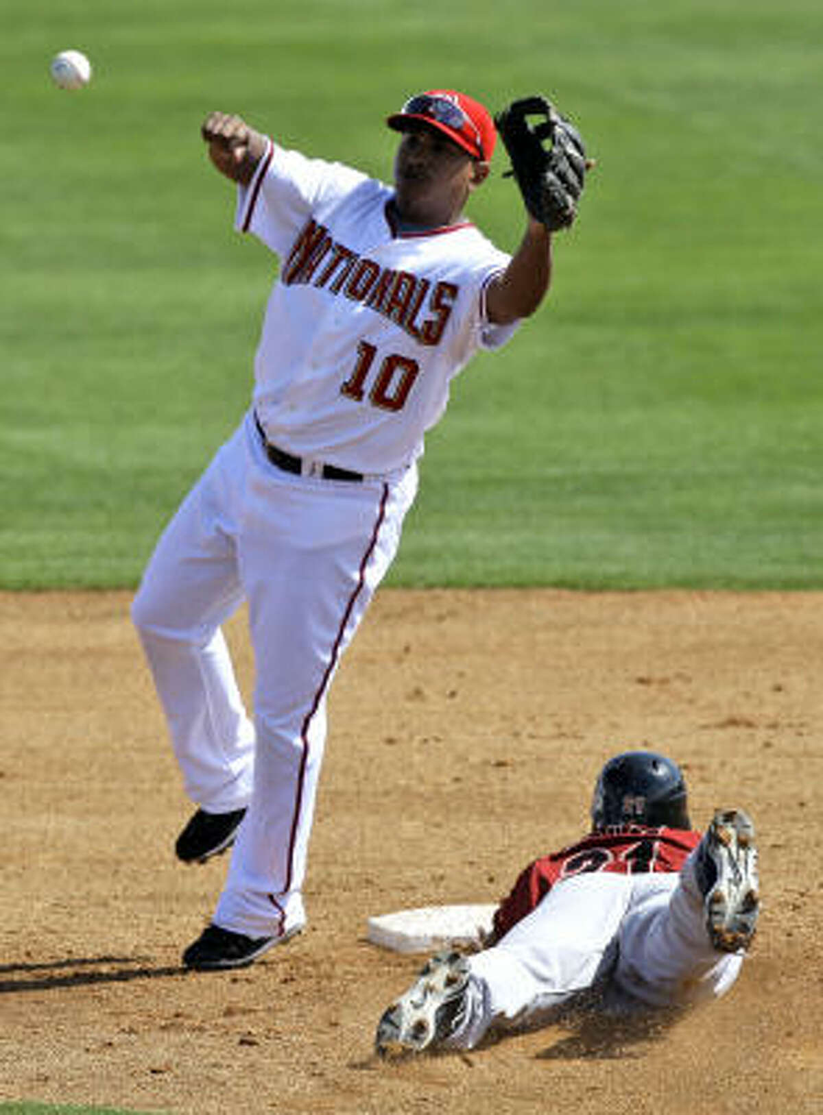 Washington Nationals second baseman Ronnie Belliard (10) reaches for the throw from catcher Jesus Flores as Houston Astros' Michael Bourn safely steals second base.