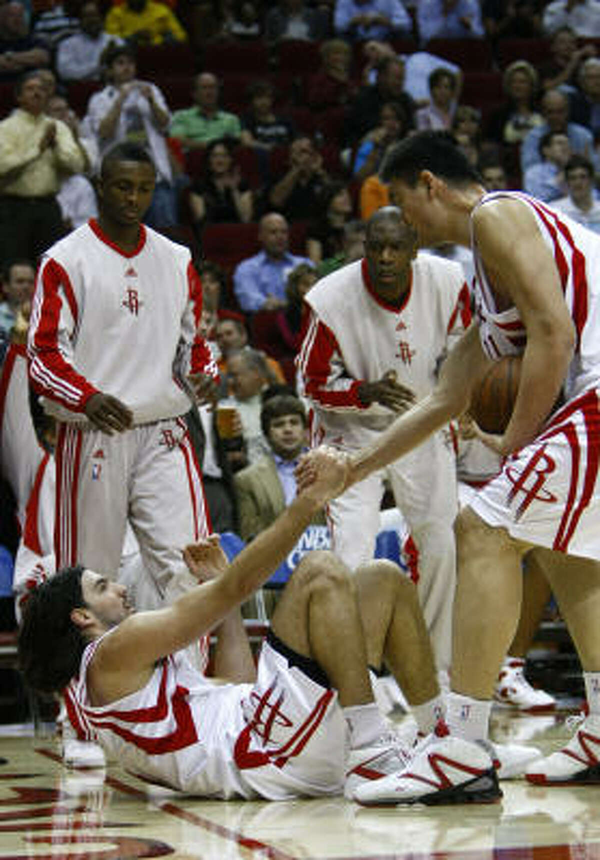 Rockets forward Luis Scola, bottom, gets a hand from teammate Yao Ming, right, after being fouled during the first quarter.