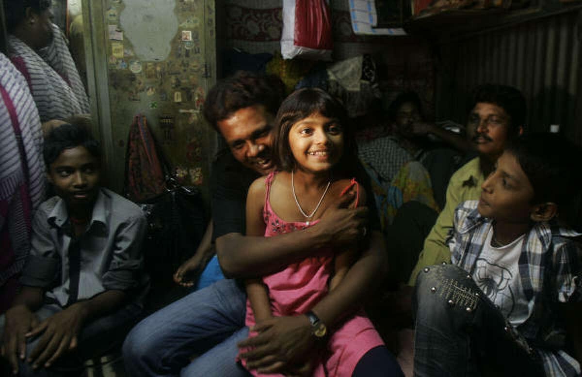 """Slumdog Millionaire"" child actor Rubina Ali, 9, center, gets a hug from her father Rafiq Asghar Ali Quereshi at her uncle's home in a slum in Bandra, in suburban Mumbai, India, Thursday."
