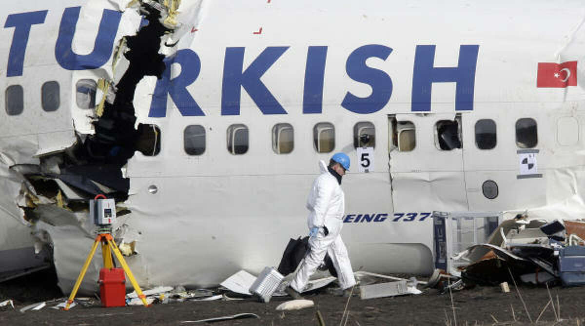 Crash investigators examine the wreckage of the Turkish airlines plane at Amsterdam's Schiphol Airport Thursday. Black box recordings recovered at the site were also being analyzed.