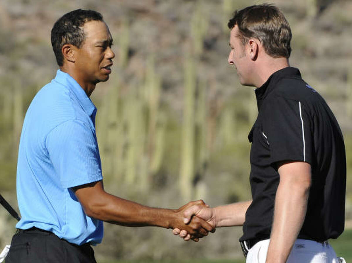Tiger Woods, left, shakes hands with Brendan Jones after Woods' 3-and-2 victory in the first round of the Accenture Match Play Championship.