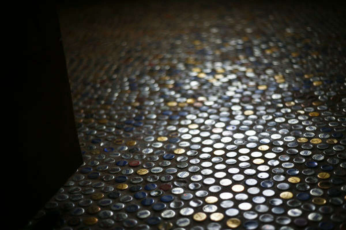 The mosaic flooring in the bedroom of Dan Phillips' Bone House was made of beer bottle caps pieced together to form a tile-like pattern.