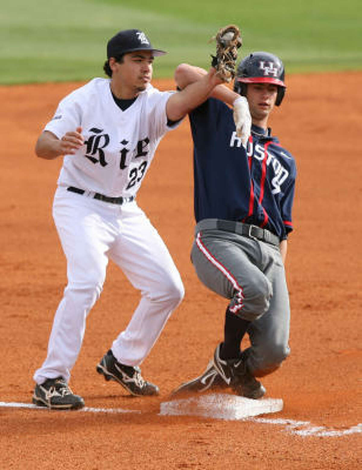 Rice third basemen Anthony Rendon (23) tags out University of Houston's Chase Dempsay (9).