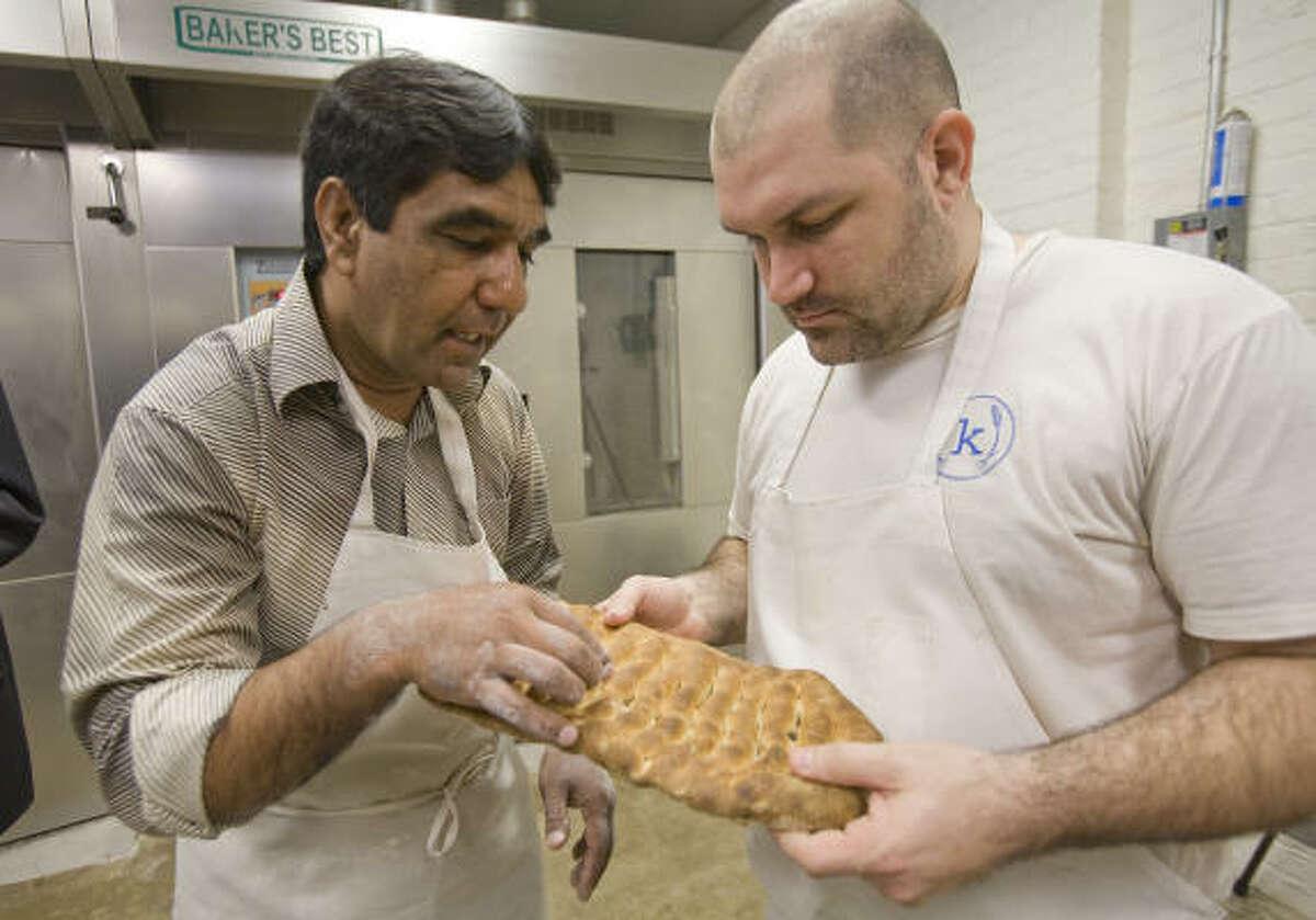 Ezatullah Sharifi shows Kraftsmen Bakery head baker Chad Fry how to bake Afghan bread Wednesday in Houston.