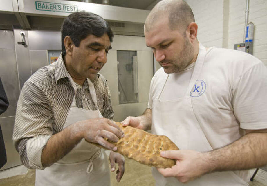 Ezatullah Sharifi shows Kraftsmen Bakery head baker Chad Fry how to bake Afghan bread Wednesday in Houston. Photo: Steve Campbell, Houston Chronicle