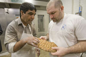 Ezatullah Sharifi shows Kraftsmen Bakery head baker Chad Fry how to bake Afghan bread Wednesday in Houston.