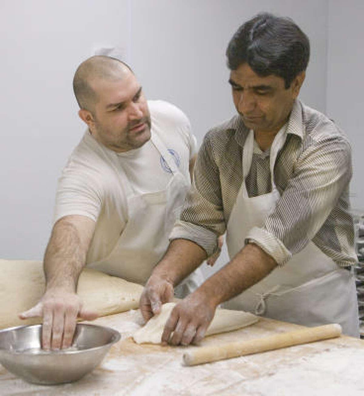Ezatullah Sharifi and Kraftsmen Bakery head baker Chad Fry make Afghan bread Wednesday in Houston.