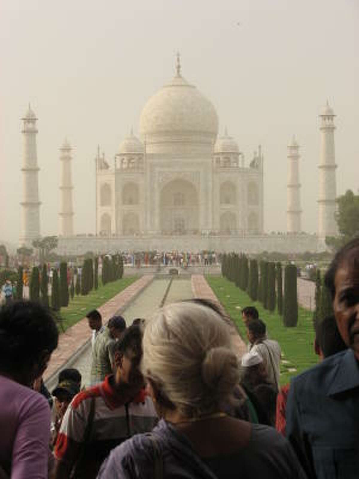 Even in a dust storm, the gardens of the Taj Mahal are packed with people.