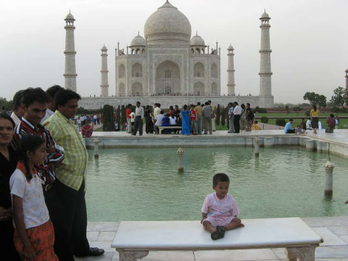 Crowds swarm the marble benches in front of the Taj Mahal, in Agra, India, waiting impatiently for their turn for a photo opt.