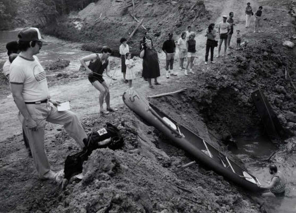 Reeking Regate participants portage thier canoe across a construciton dam at Chimmney Rock and Buffalo Bayou in the '70s.