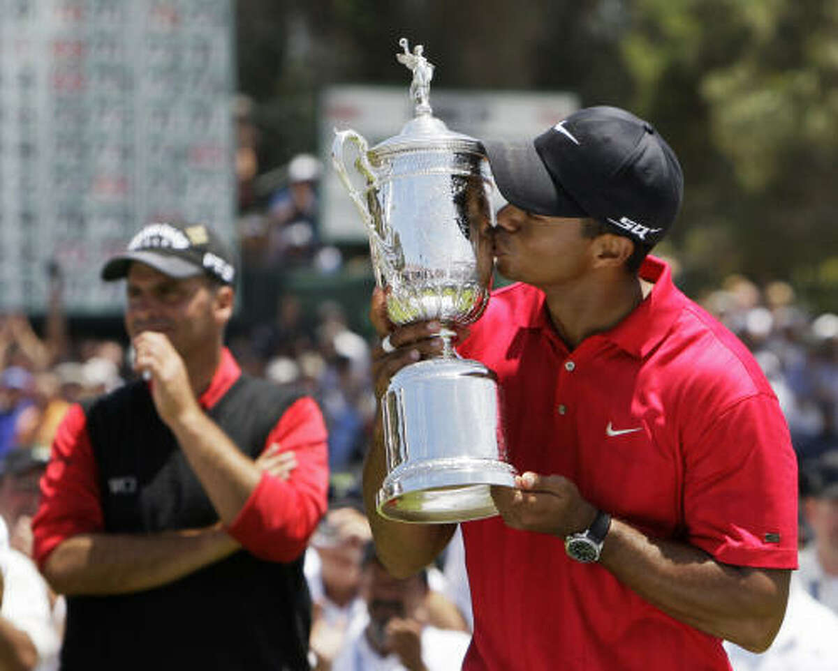 2008 U.S. OPEN: Tiger Woods got to lay his lips on the U.S. Open trophy for the third time after a thrilling sudden-death win against Rocco Mediate, left.