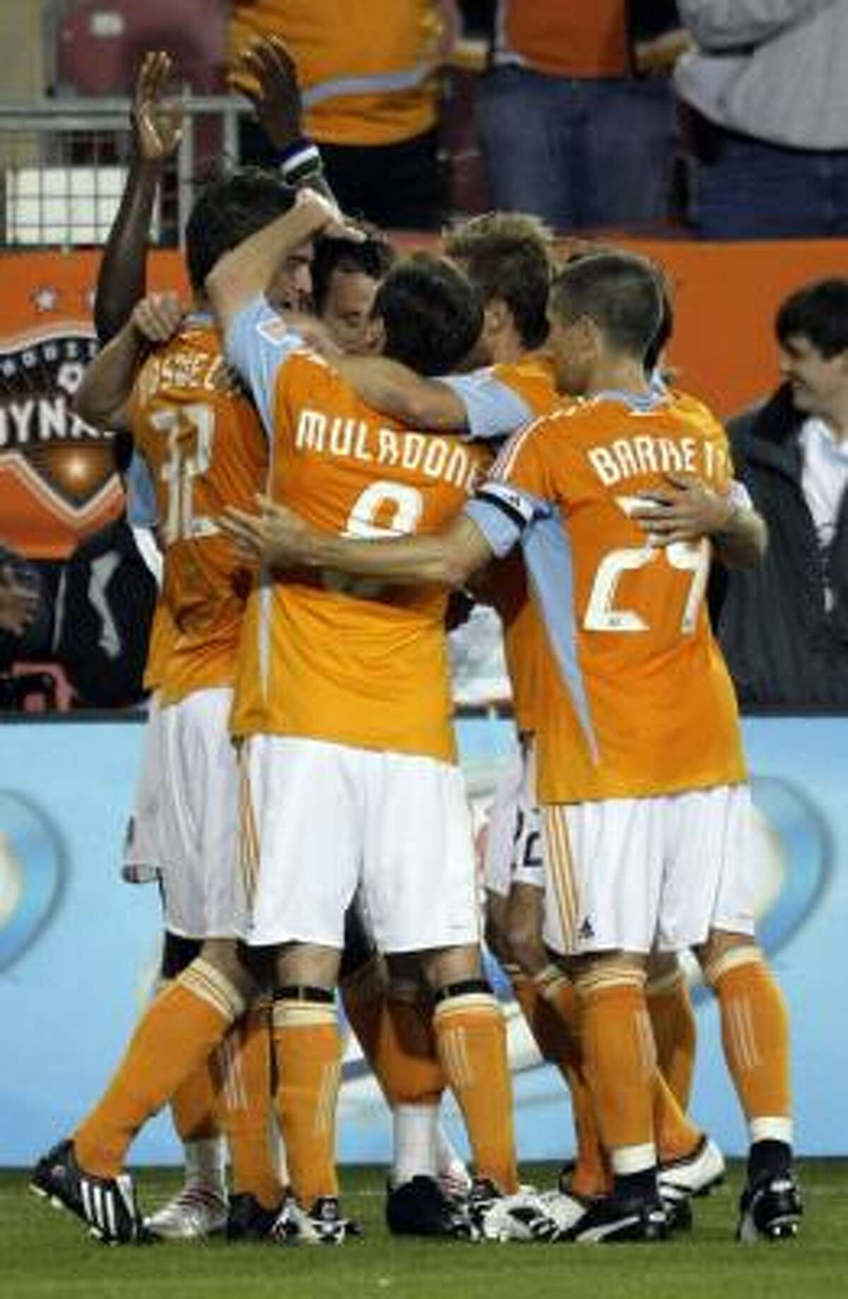 Dynamo defender Bobby Boswell, left, is mobbed by teammates Richard Mulrooney, center, and Wade Barrett after scoring during the first half.