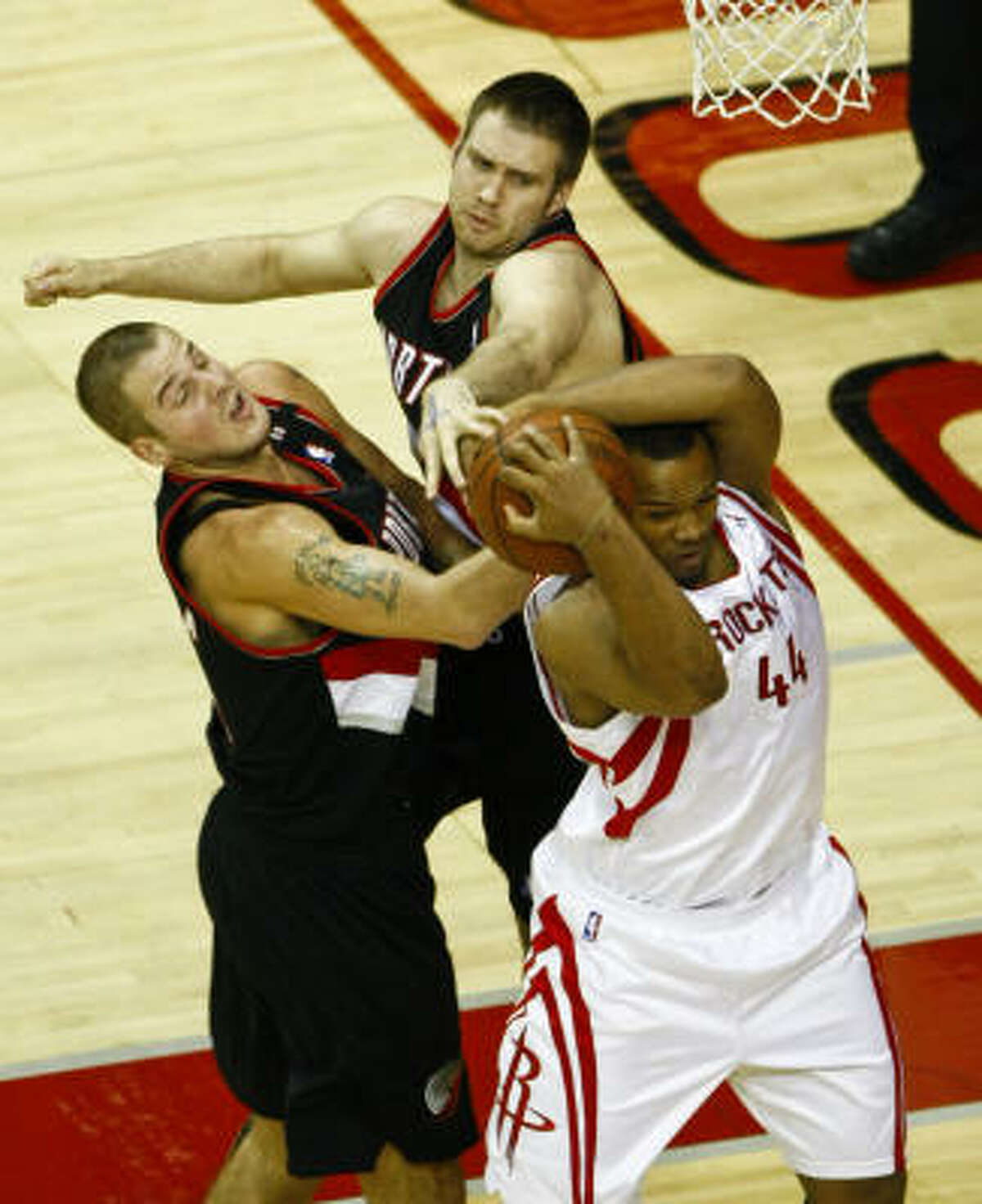 Chuck Hayes (44) battles with Portland's Sergio Rodriguez (11) and Shavlik Randolph (42) during the first quarter.