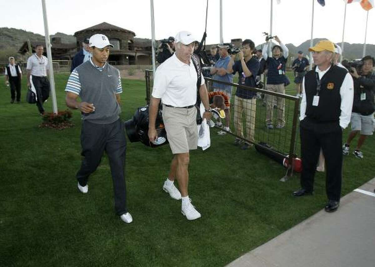 Tiger Woods, left, and caddy Steve Williams head to the driving range before playing a practice round at the Accenture Match Play Championship.