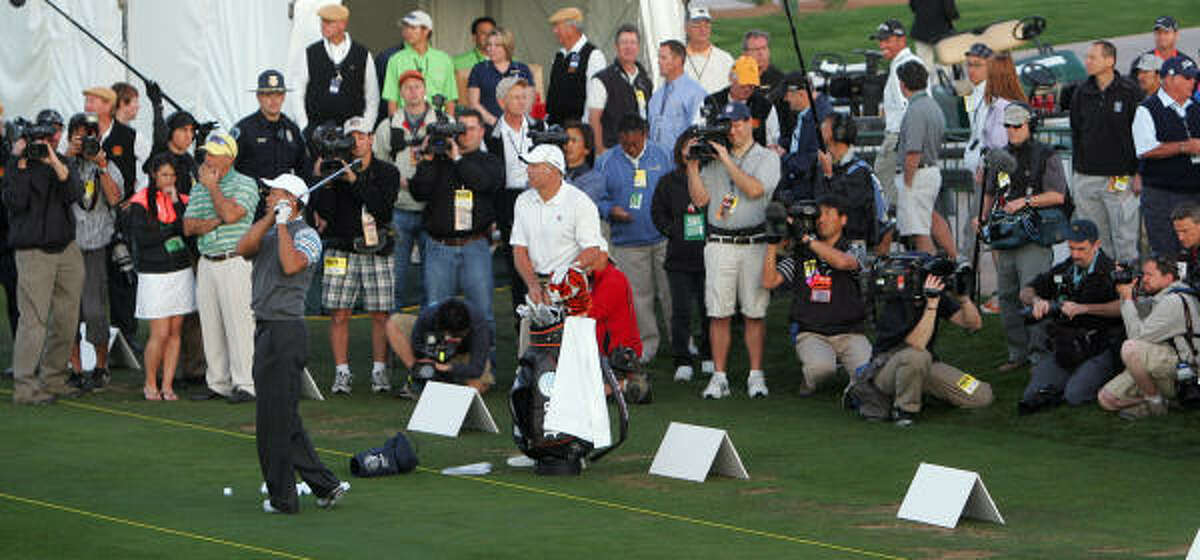 With a host of media members looking on, Tiger Woods tees off on the practice range before beginning his round.