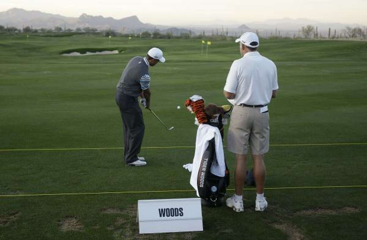 Tiger Woods hits a few practice shots as caddy Steve Williams watches.