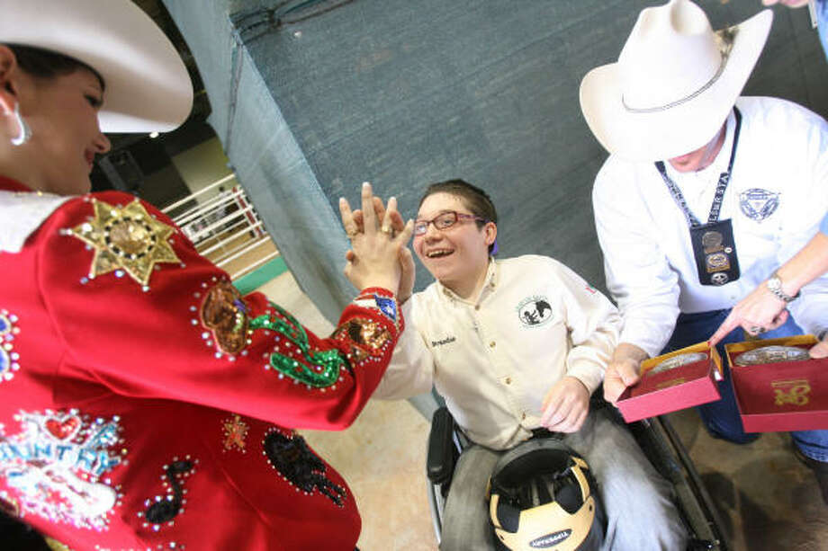 RODEO FUN: Miss Rodeo Texas Avery Gonzalez congratulates Brandon Rys, 16, for winning first place in the Western category at the Houston Livestock Show and Rodeo's Top Hands Horse Show in Houston. The event involved Leap of Faith, a horse-assisted therapy program at the Conroe Family YMCA. Photo: Mayra Beltran, Chronicle