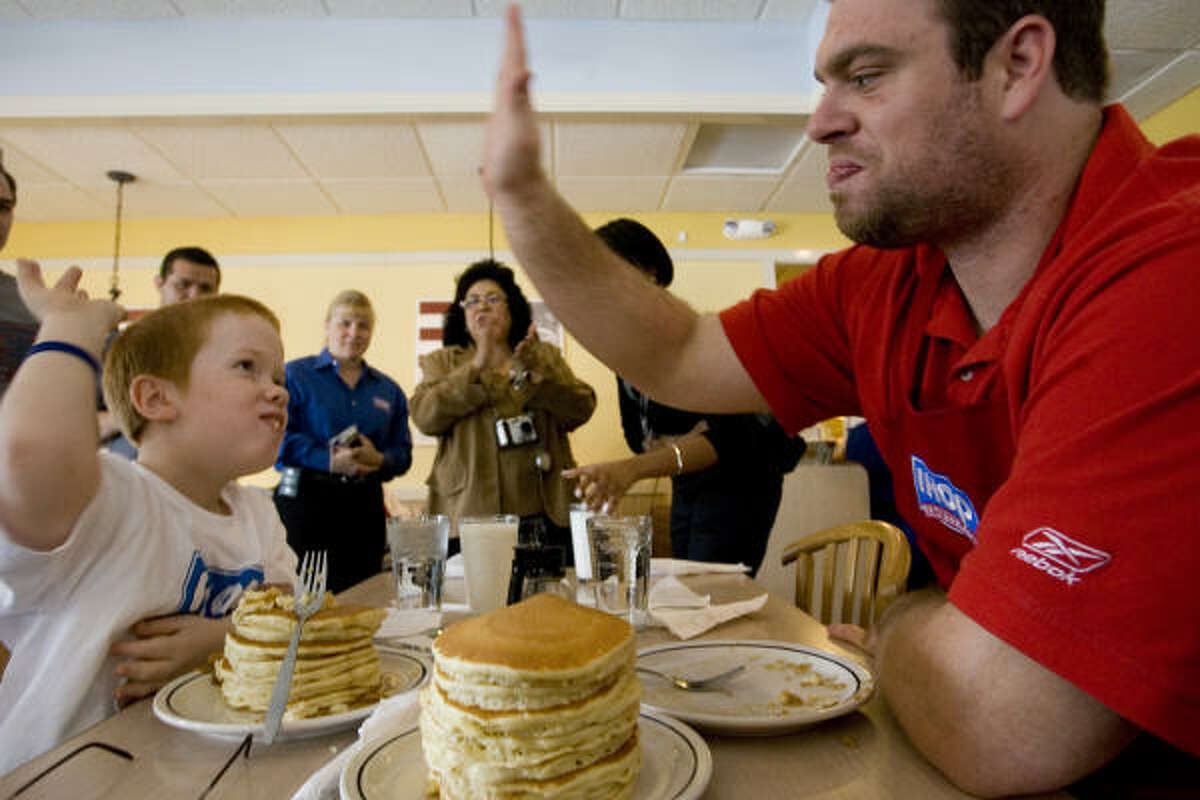 Texans offensive lineman Eric Winston high-fives Duncan Wells, 10, following a pancake-eating contest at IHOP. Duncan is a patient at Shriners Hospitals for Children.