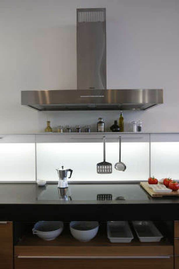 Glass-top pullout trays are showy but functional. Photo: Julio Cortez, Chronicle