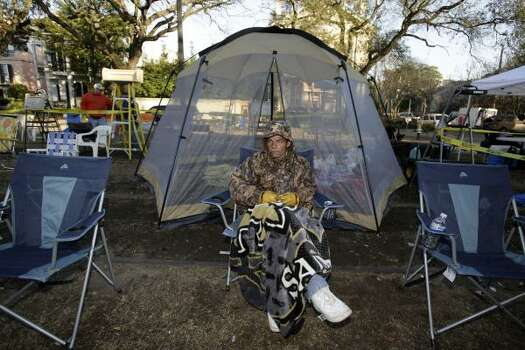 James McClendon from New Orleans, is bundled up with temperatures in the 40's as Pete Fountain and his Half Fast Walking Club march onto St. Charles Avenue in the Garden District of New Orleans on Tuesday. Photo: Alex Brandon, AP
