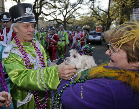 """Gisele LaRose, with her dog """"Coucon de Lait,"""" gets beads from members of Pete Fountain and his Half Fast Walking Club as they march to St. Charles Avenue in the Garden District of New Orleans on Tuesday. Photo: Alex Brandon, AP"""