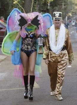 """A woman who called herself only """"Madam Butterfly,"""" walks with a member of Pete Fountain and his Half Fast Walking Club on St. Charles Avenue in the Garden District of New Orleans Tuesday. Photo: Alex Brandon, AP"""