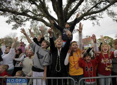 Parade-goers yell for beads and other trinkets as Kid Rock's float goes by during the Krewe of Endymion parade in New Orleans on Saturday, Feb. 21, 2009. Photo: Alex Brandon, AP