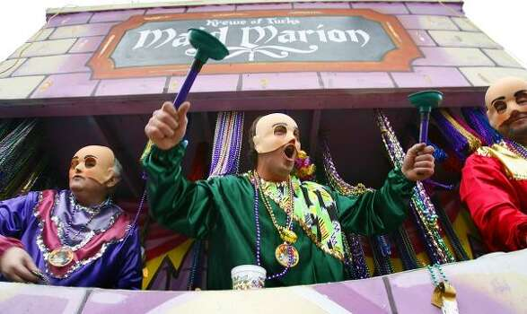 Holding a couple of their signature plunger throws, a rider on a float titled Tucks - The Mother of All Parades, teases the crowds on St. Charles Avenue on Saturday, Feb. 21, 2009, in New Orleans. Photo: CHRIS GRANGER, AP