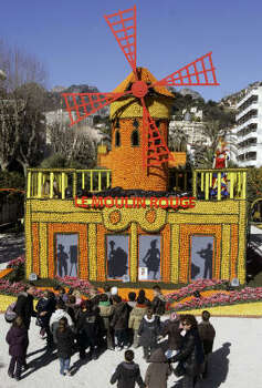 Children look at a windmill made with lemons and oranges representing the famous Parisian cabaret Le Moulin Rouge during the lemon festival in Menton, southern France, on Feb. 13, 2009. Some 145 metric tons of lemons and oranges are used to make displays during the festival, which is themed The Music of the World. Photo: LIONEL CIRONNEAU, AP