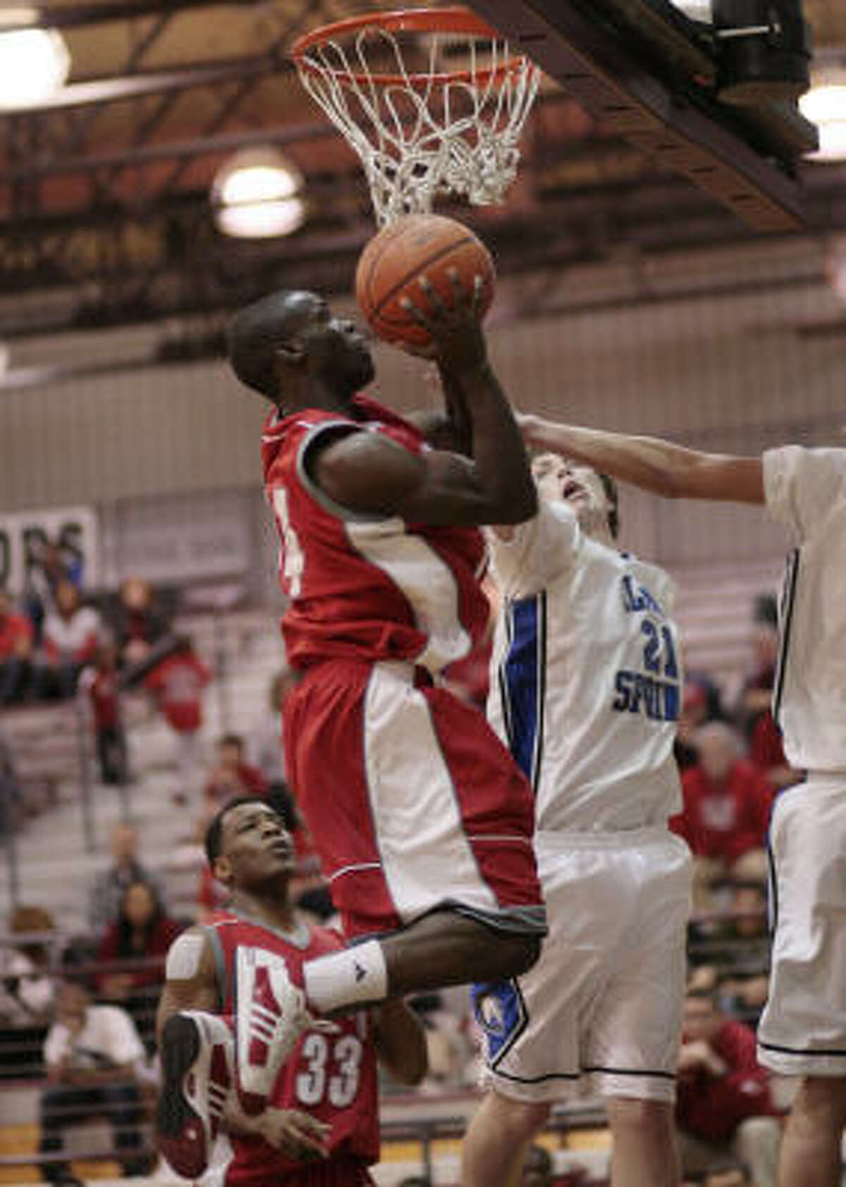 Travis guard Ray Penn drives for a layup as Clear Springs' Anthony Horton attempts to block the shot.