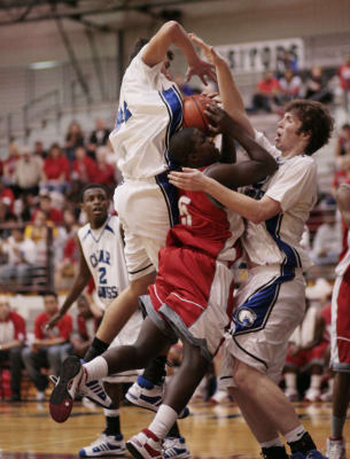 Travis' Denzel Billy is sandwiched by Clear Springs' Anthony Horton, right, and Ryan Garcia as he drives to the basket.