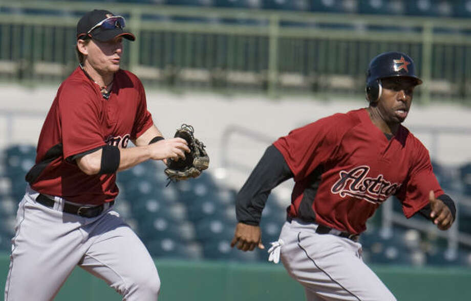 Chris Johnson left chases Michael Bourn (right) in a drill during the Houston Astros spring training at Osceola County Stadium. Photo: James Nielsen, Chronicle