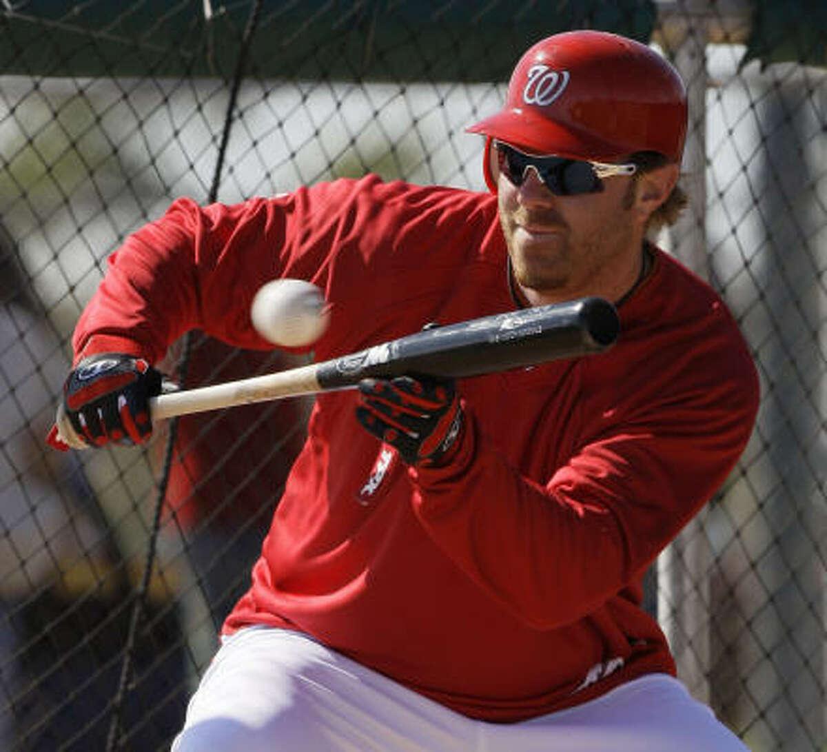 Washington Nationals first baseman Adam Dunn bunts a pitch during a spring training baseball workout.