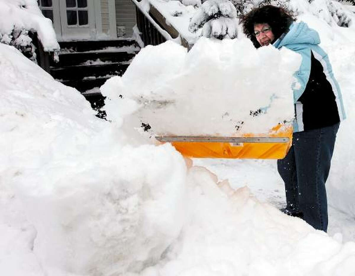 Patricia Hewins tosses a shovel full of snow while clearing a walk at her home in Waterville, Maine, after 15- inches of snow fell overnight. Asked how she feels about all the snow, Hewins said,