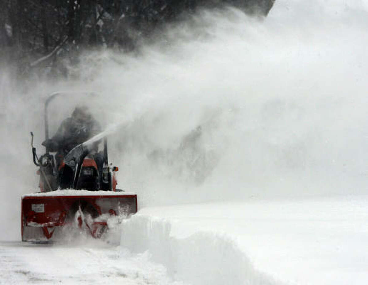 Malcolm Joslin clears his driveway in Berlin, Vt., Monday. Snow is expected to continue today in the mountains of northern and central Vermont, where a total of 10 to 20 inches is expected.