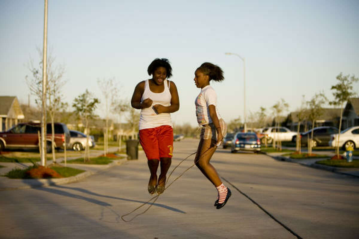 Children like Monet Walter, left, and Colisha Preston play on the street because a promised community center has yet to be built.