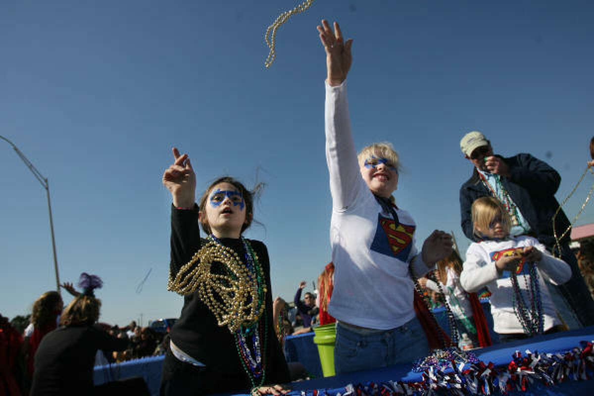 Catherine Haver, 8, and Megan Leasure toss beads at one of Galveston's Mardi Gras parades over the weekend.