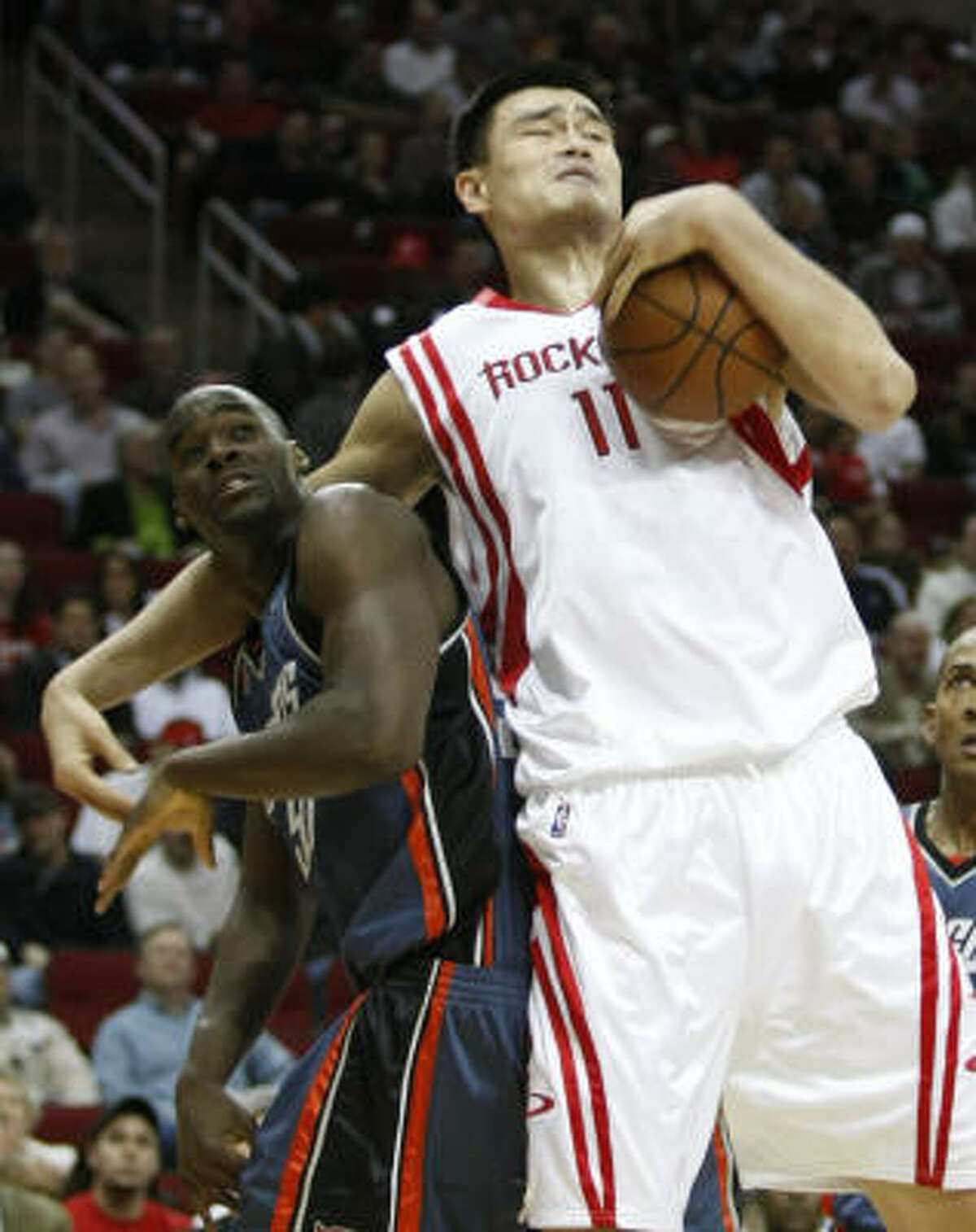 Yao Ming (11) grabs a rebound over Bobcats center Emeka Okafor in the first half. Yao scored 19 points to go along with seven rebounds.