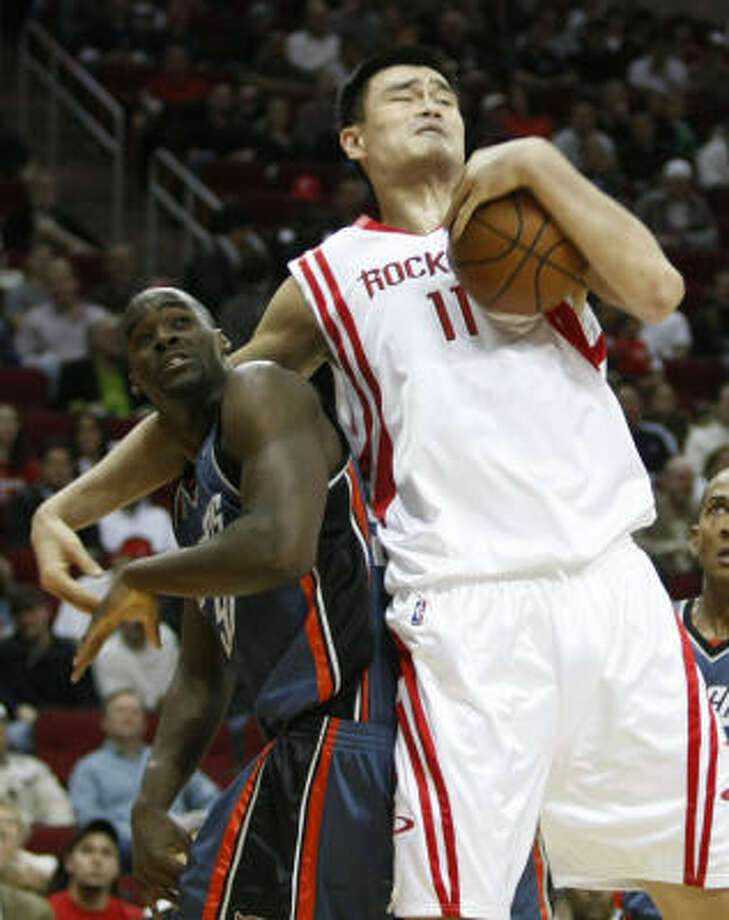 Yao Ming (11) grabs a rebound over Bobcats center Emeka Okafor in the first half. Yao scored 19 points to go along with seven rebounds. Photo: Brett Coomer, Chronicle