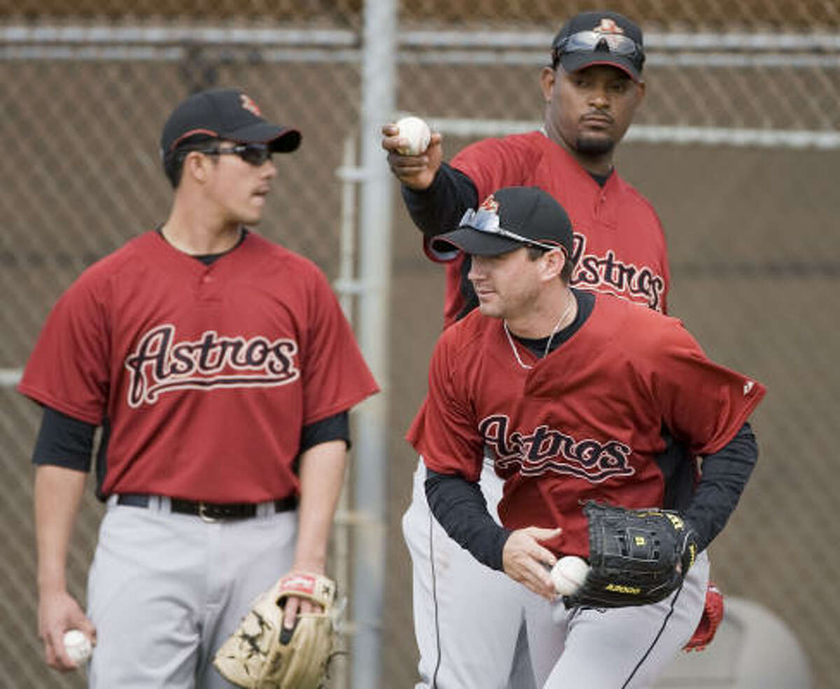 Jose Valverde (upper right) holds a ball over Brian Moehler (lower right) as Sergio Perez (left) looks on.