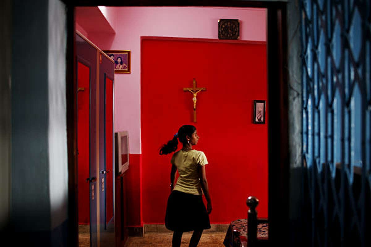 A resident walks through a bedroom to the kitchen at the Sharanam Home for Girls in Dharavi, Mumbai.