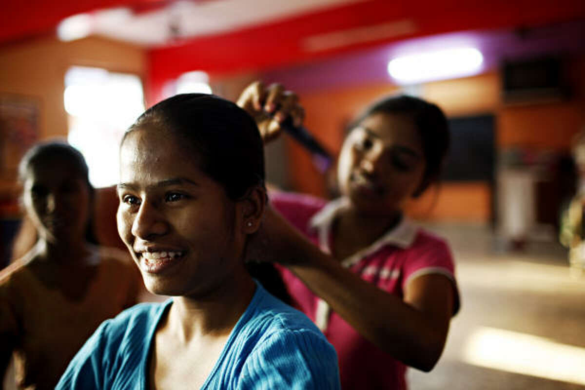 Bharti has her hair combed and braided by Neelam at the Sharanam Home for Girls in Dharavi, Mumbai.