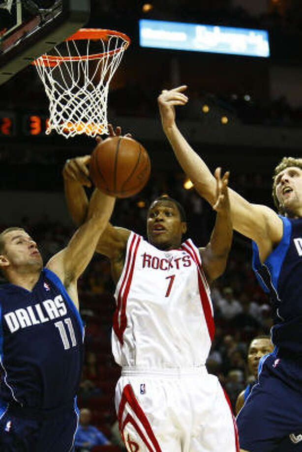 Kyle Lowry, center, tries to get control of a rebound as Dallas' Jose Juan Barea, left, and Dirk Nowitzki defend in the second quarter. Lowry played his first game in Houston since being traded from the Grizzlies in a three-team deal Thursday that included the Orlando Magic. Photo: Michael Paulsen, Chronicle