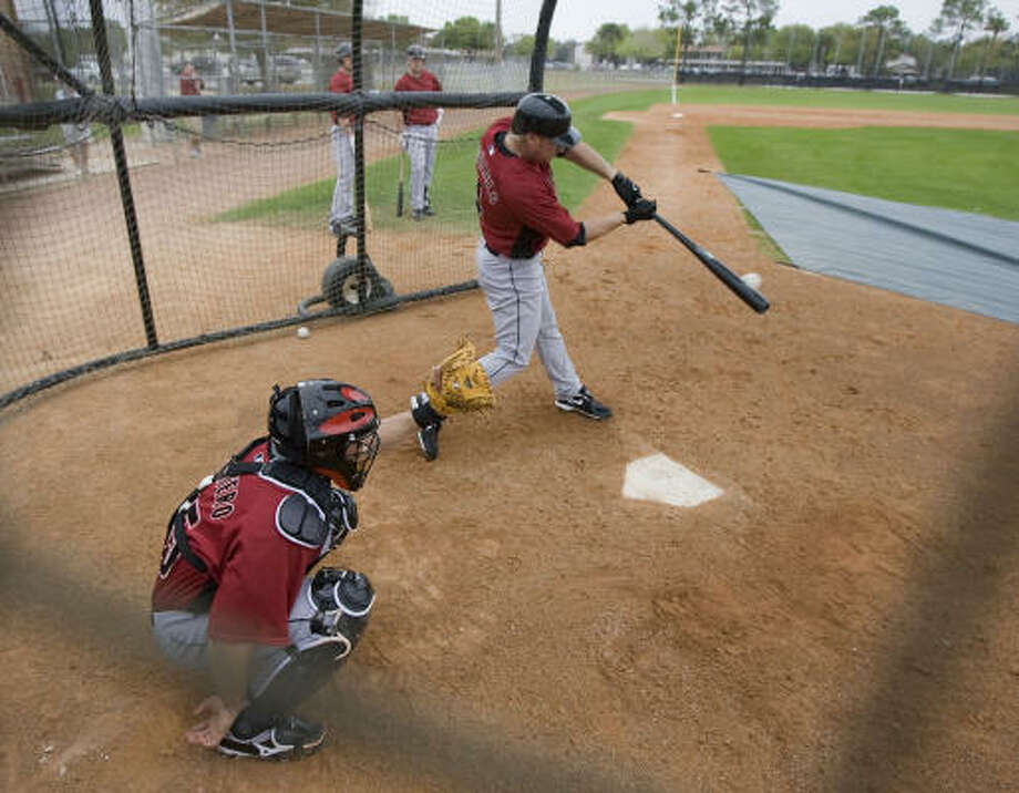 Humberto Quintero (left) catches as Jason Michaels hits the ball during live batting practice at Thursday's spring training workout at Osceola County Stadium in Kissimmee, Fla. Photo: James Nielsen, Chronicle