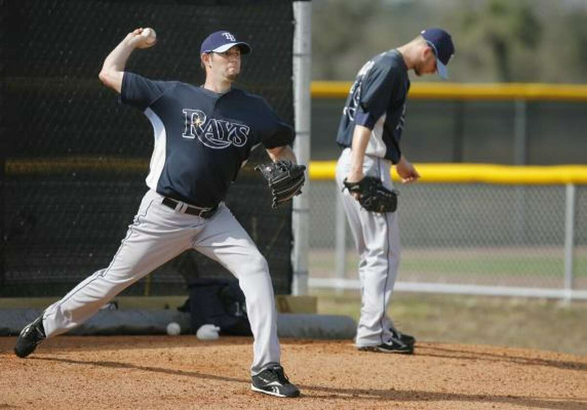 Tampa Bay's Jason Hammel, left, and J.P. Howell, right, pitch off the mound during spring training drills.