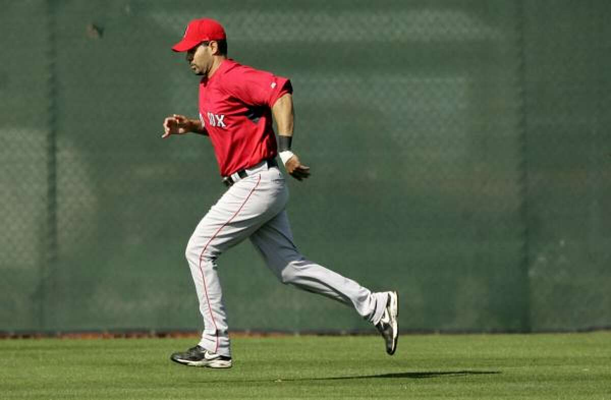 Boston Red Sox third baseman Mike Lowell runs on a practice field during a spring training workout. Lowell is recovering from hip surgery.