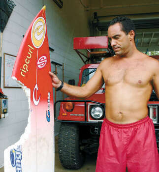 Firefighter Tim Terrazas shows the board that surfing star Bethany Hamilton was on when she was attacked by a shark on Oct. 31, 2003 off Kauai in Hawaii. The shark bit a chunk out of the board measuring about 16 inches across and 8 inches deep. Photo: DENNIS FUJIMOTO, AP