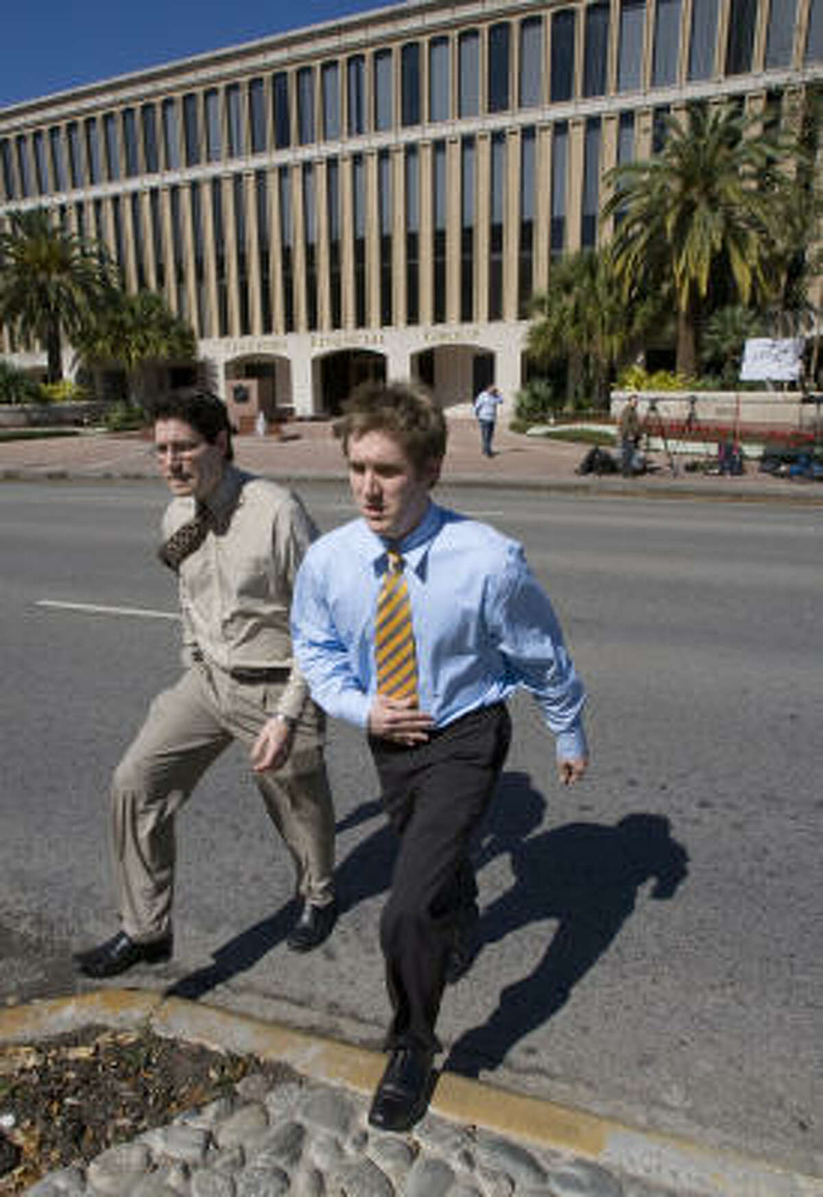 Two investigators cross Westheimer after leaving the locked offices of Stanford Financial Group at 5050 Westheimer Thursday in Houston.