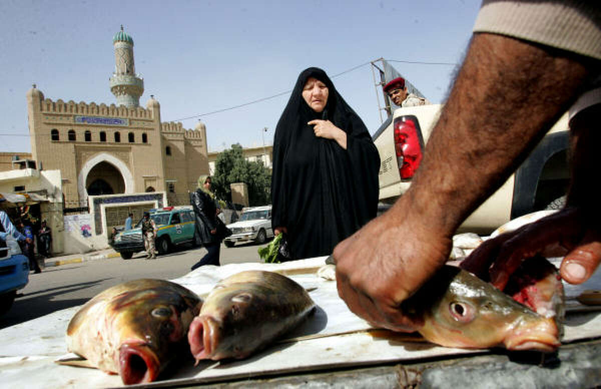 An Iraqi fishmonger offers a fish for sale at the newly opened Shuhada fish market Thursday in Baghdad.